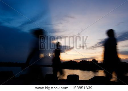 Silhouette and motion blur of people walking at riverside in evening,Cloud Shadow with blue sky