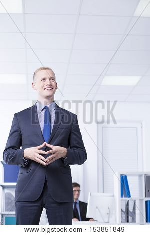 Shot of smilled man in suit standing proudly in bright room interior