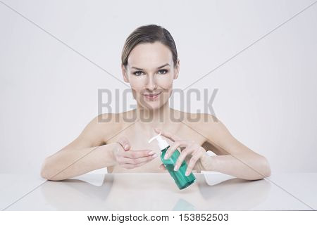Young woman with naked body using the liquid soap