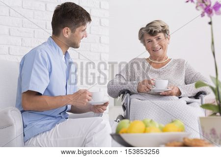 Elder Woman On A Wheelchair With Cup Of Tea