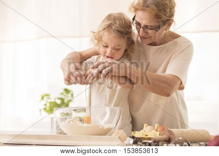 Child Breaking The Egg Into A Bowl