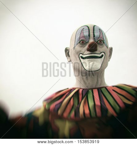 The creepy clown looms in your nightmares - Filtered clown statue at a festival carnival poster