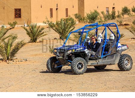 Itrane Morocco - Feb 24 2016: blue Polaris RZR 800 with woman pilot in a small Berber village in Morocco desert near Merzouga