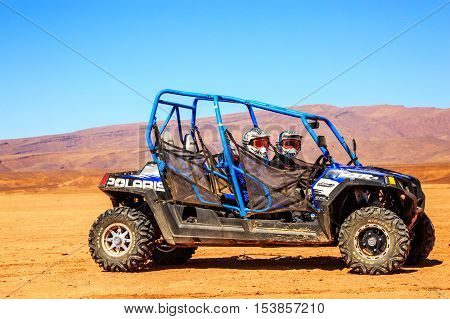 Merzouga Morocco - Feb 22 2016: Side view on blue Polaris RZR 800 with it's pilots in Morocco desert near Merzouga. Merzouga is famous for its dunes the highest in Morocco.