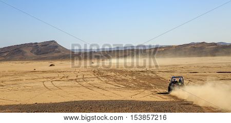 Merzouga Morocco - Feb 25 2016: panoramic view on convoys of offroad cars in Morocco desert near Merzouga. Merzouga is famous for its dunes the highest in Morocco.