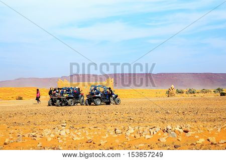 Merzouga Morocco - Feb 26 2016: back view on group of off-road pilots during a break in berber village on Morocco desert near Merzouga. Merzouga is famous for its dunes the highest in Morocco.