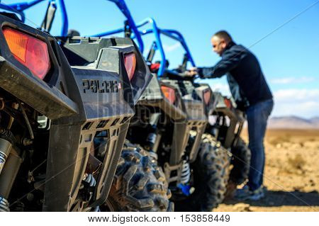 Merzouga Morocco - Feb 21 2016: blue Polaris RZR 800 aligned and stationed with no pilot in Morocco desert near Merzouga. Merzouga is famous for its dunes the highest in Morocco.