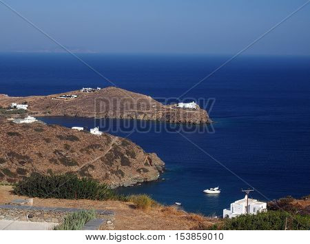 church monastery on promontory in Aegean Sea with houses and boat Sifnos Greek Island Cyclades in Greece