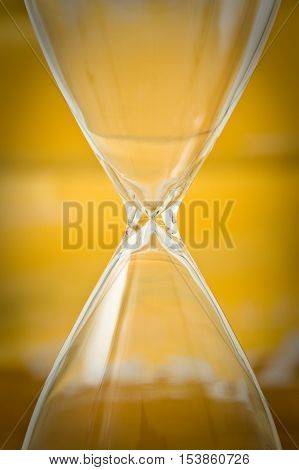 Empty hourglass on yellow background - concept image