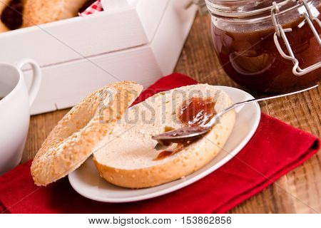 Sesame bagels with jam on white dish.