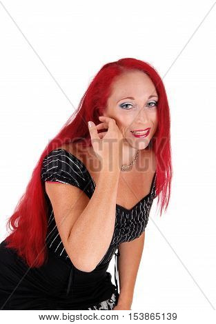 A closeup portrait of a woman with long red hair and a black dress bending forward isolated for white background.
