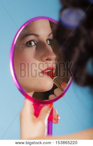 young woman preparing to party getting ready for going out. Girl styling hair with curlers applying make up red lipstick looking at mirror retro style blue background