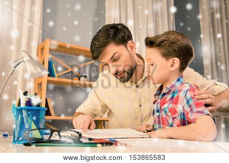 Father and son sitting at the table and reading on new year holidays