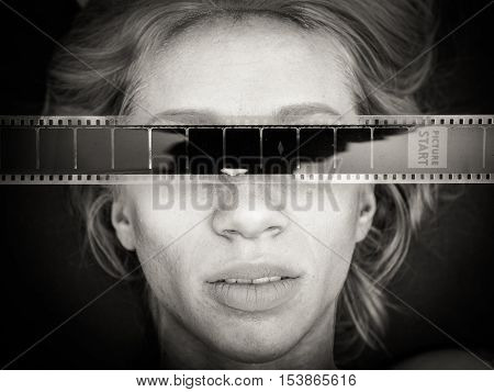 Young woman human face with filmstrip on eyes black and white