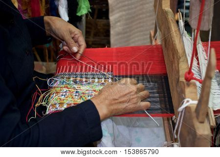 Old woman weaving red black and multi color cotton flag pattern on loom in North of Thailand