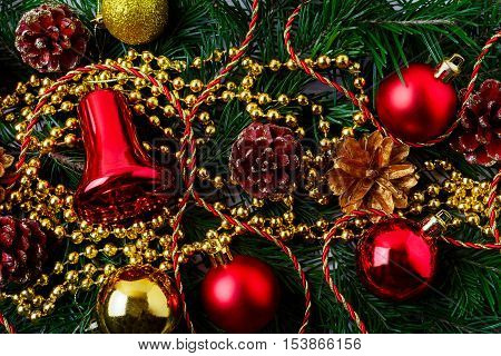 Christmas background with golden pinecone and red ornaments. Christmas party decoration with shiny balls. Christmas greeting background.
