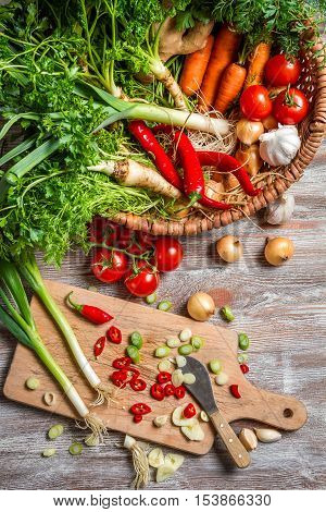 Basket full of fresh vegetables on old wooden table