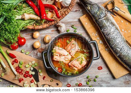 Fresh ingredients for fish soup on old wooden table