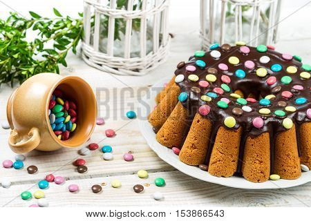 Decorating traditional easter cake with candies on old wooden table