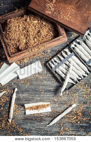 Homemade cigarettes made with tobacco on old wooden table