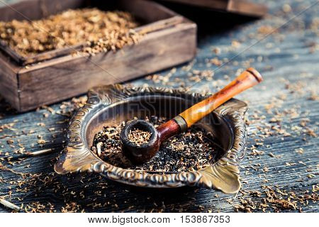 Closeup of wooden pipe with tobacco on old wooden table