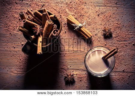 Cocoa with milk and cinnamon flavored on old wooden table