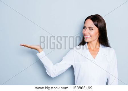 Smiling Assistant  Holding Something On Hand And Demonstrating It