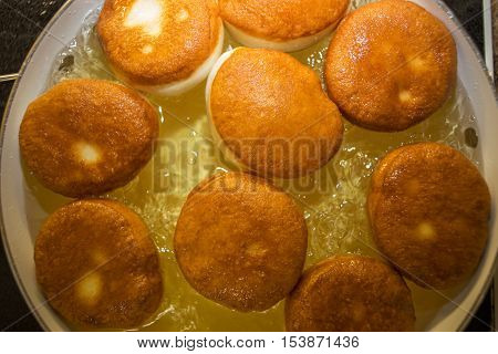 A frying pan with hot bubbling oil full of browned donuts without the holes