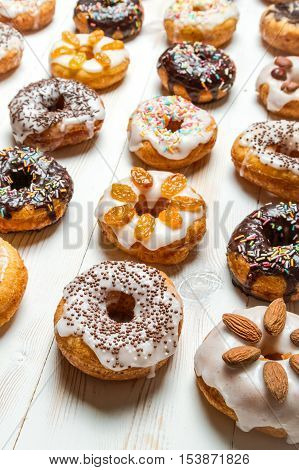 Large group of glazed donuts on old wooden table