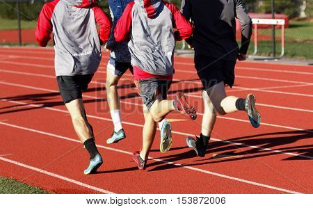 A group of boys training for cross country on a track