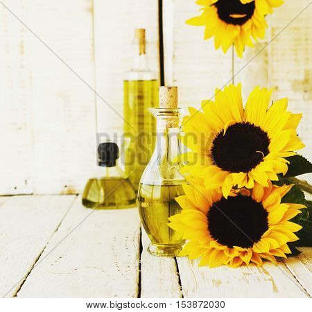 Bottle with sunflower oil standing on the white table with vintage flowers sunflower, selective focus