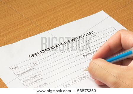 Filling for application for employment form on wooden table