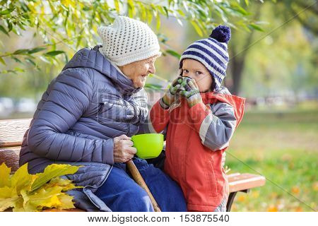 Senior woman and her great grandson drinking hot tea in autumn park