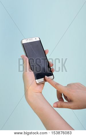 Bangkok Thailand September 10 2016 : Woman held android phone Samsung galaxy S7 Edge on blue concrete background. Samsung S7 Edge is smart phone with multi touch screen