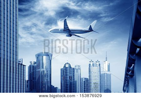 The plane flew over high-rise buildings in modern cities.