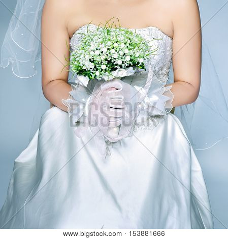 Wearing bridal flowers holding the bride, partial close-up.