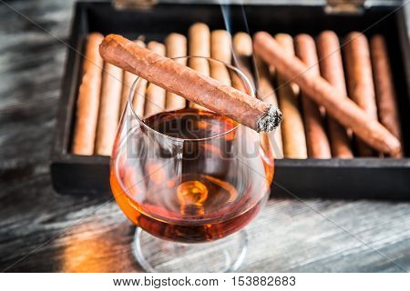 Burning cigar on glass with cognac on old wooden table