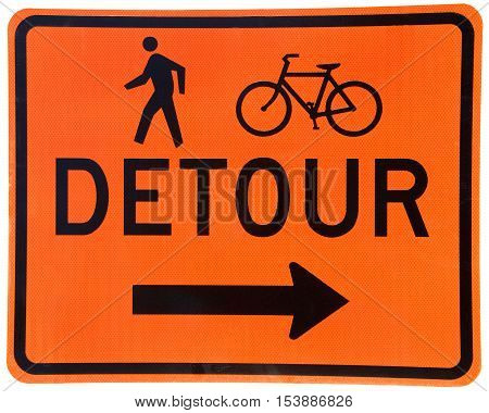 Detour sign black text on orange background pedestrians and bicyclists arrow pointing to the right. Textured sign.