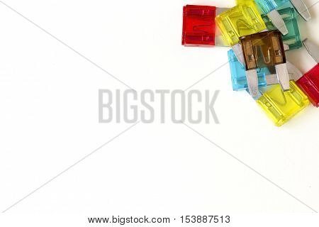 The fuse of the car. Pile of colorful electric automotive fuses or circuit breakers, on a light table for background