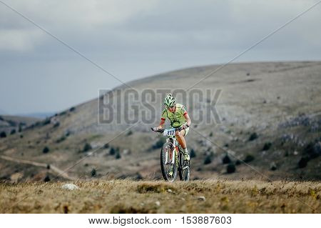 Privetnoye Russia - September 21 2016: female athlete a cyclist riding uphill on a bicycle during Crimean race mountainbike