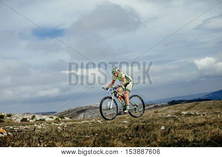 Privetnoye Russia - September 21 2016: female athlete mountainbiker rides on mountain against sky on a bike during Crimean race mountainbike