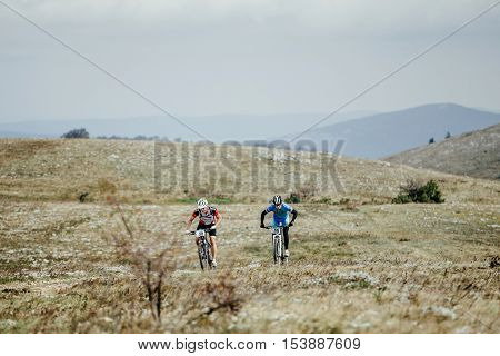 Privetnoye Russia - September 21 2016: two riders cyclists ride plain to mountains during Crimean race mountainbike