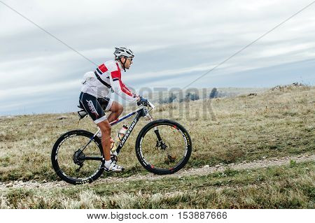 Privetnoye Russia - September 21 2016: male cyclist mountainbiker sports bike rides on a mountain trail during Crimean race mountainbike