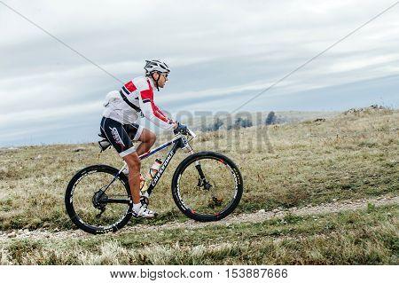 Privetnoye Russia - September 21 2016: male cyclist mountainbiker sports bike rides on a mountain trail during Crimean race mountainbike