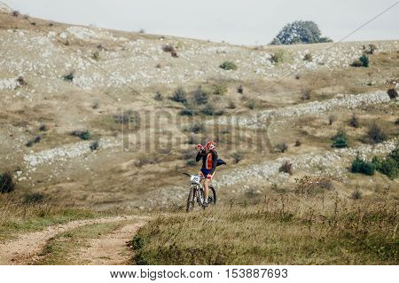 Privetnoye Russia - September 21 2016: racer cyclist on mountain bike drinking water from a bottle during Crimean race mountainbike