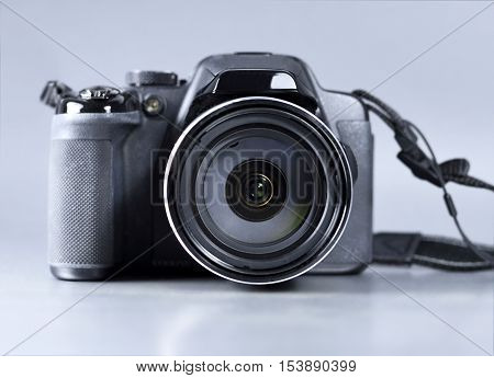 Front view of a digital camera or bridge camera, studio shot.