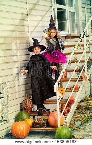 Happy children in a costumes of witches and wizards celebrating halloween. Trick or treat. Halloween party.