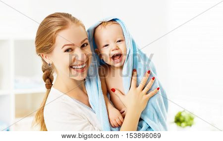Happy family mother and baby in a blue towel after bathing in the bath