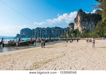KRABI - JANUARY 20, 2015 : Tourist enjoying a beach walk on a sunny day JANUARY 20, 2015 at Railay Beach in Krabi, Thailand. Railay Beach is a small peninsula with white sand beaches, soaring limestone cliffs, viewpoints, caves and a lagoon hidden inside