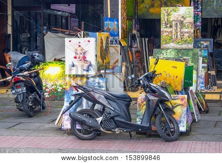 UBUD BALI - OCTOBER 12 2016: Colorful paintings and scooters outside an artists studio in Ubud in Central Bali Indonesia.